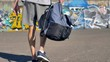 A graffitist takes a backpack with paints in one hand.