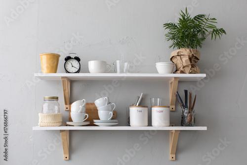 Fotografía  Utensils and mugs on shelf