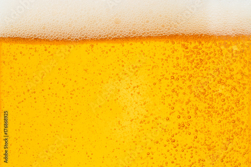 Pouring beer with bubble froth in glass for background