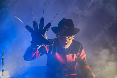 man is a serial killer with a glove sharp knives background for Halloween Canvas Print