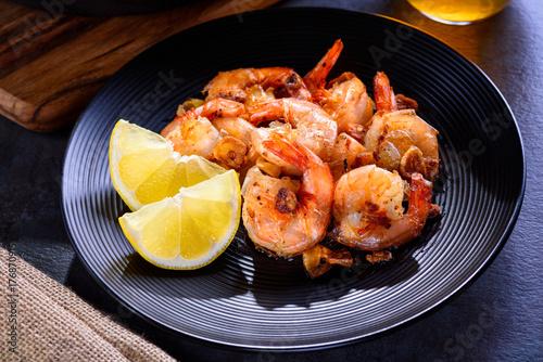 Photo Skillet roasted jumbo shrimp on a black plate