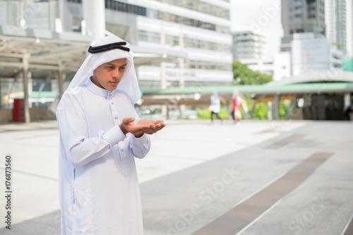 Zdjęcie XXL Muzułmański mężczyzna modlenie miejsce publicznie i nowożytny budynku tło