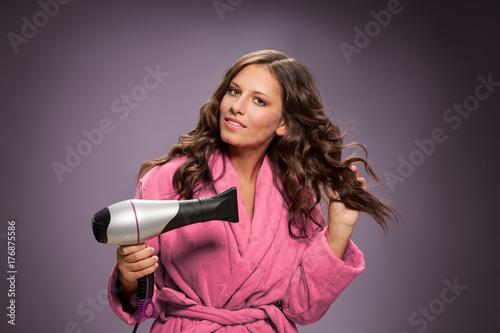 Plakat młoda kobieta wysusza włosy