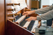 canvas print picture - Close up view of a organist playing a pipe organ