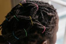 Black Girl's Hair Braided With Colorful Rubber Bands