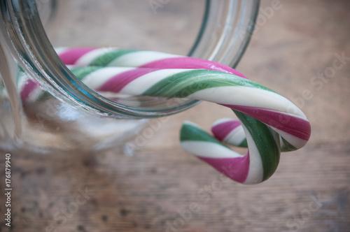 Fotografie, Obraz  bonbons traditionnels de noël en forme de canes dans un bocal en verre sur table