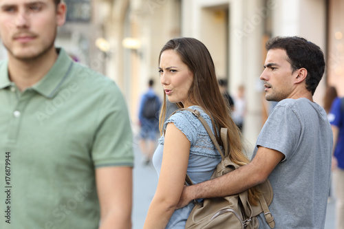 Photographie Disloyal woman looking another man and her angry boyfriend