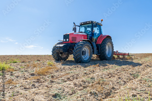 agricultural tractor in the foreground with blue sky background. Obraz na płótnie