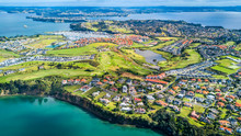 Aerial View On Residential Suburbs Surrounded By Sunny Ocean Harbour. Whangaparoa Peninsula, Auckland, New Zealand