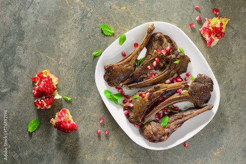 Lamb chops with pomegranate and mint leaves served in a plate