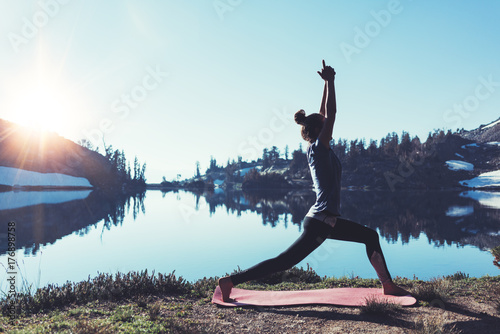 Fotografia  Gorgeous young happy traveling girl practicing yoga outdoor in the stunning mountain wilderness in front of amazing cold lake