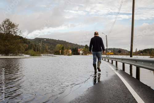 Plakat Mężczyzna odprowadzenie na zalewającej drodze, woda przychodzi od rzecznego Tovdalselva w Drangsholt w Kristiansand Norwegia, Październik, - 3, 2017.