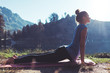 Leinwandbild Motiv Fit young happy traveling girl practicing yoga outdoor in the stunning mountain wilderness in front of amazing cold lake at sunrise. Calmness and relax, female happiness.