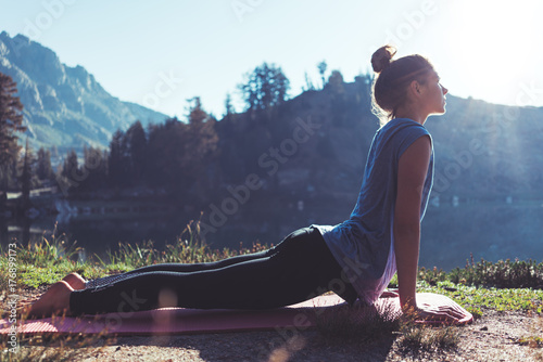Stampa su Tela  Fit young happy traveling girl practicing yoga outdoor in the stunning mountain wilderness in front of amazing cold lake at sunrise