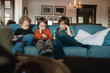 Three boys sitting on couch watching tablet