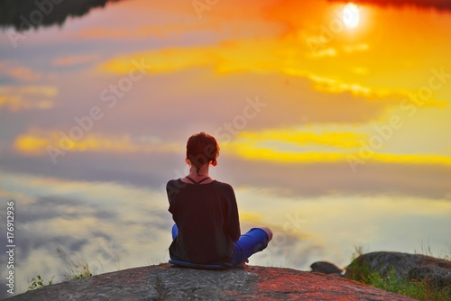 Foto  Young woman sitting on the stone enjoying peaceful moment of sunset