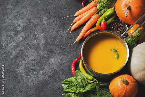 Plakat Kremowa zupa dyniowa z warzywami na czarnym tekstury.
