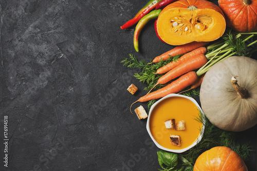 Plakat Kremowa zupa dyniowa z warzywami na czarnym tekstury