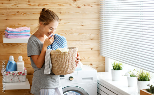 Photo  Happy housewife woman in laundry room with washing machine  .