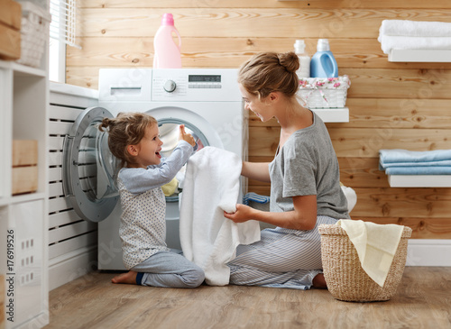 Happy family mother housewife and child   in laundry with washing machine Canvas Print
