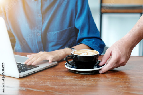 Male waiter hand serving a cup of coffee while customer working with laptop comp Canvas-taulu
