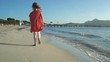 Little girl in bright red dress running on the beach barefoot