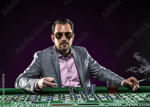 Gambler playing roulette smoking плакат