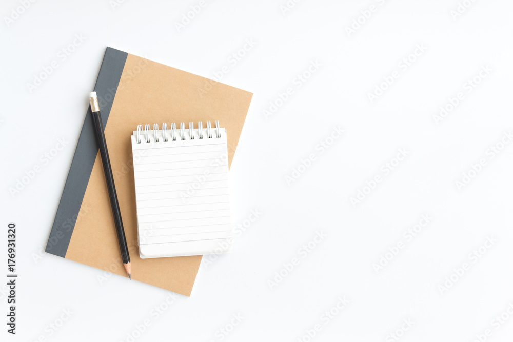 Fototapeta black pencil and notebook paper on brown notebook paper on white background