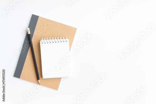Obraz black pencil and notebook paper on brown notebook paper on white background - fototapety do salonu