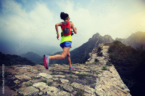 Obraz na plátně  fitness woman trail runner running at great wall on the top of mountain