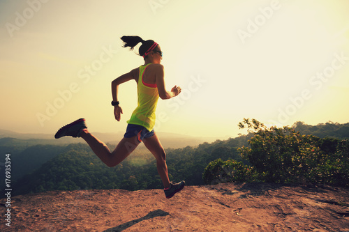 Poster Glisse hiver Young fitness woman trail runner running at mountain top