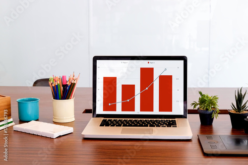 Computer Desktop On Office Table Showing Charts And Graph Against