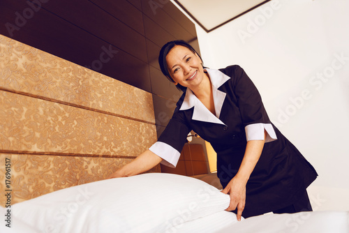 Positive delighted chambermaid working in luxury room
