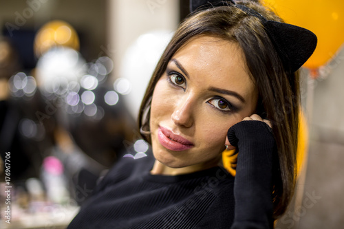 Fotografie, Obraz  a portrait of a beautiful young girl in a cat suit Halloween masquerade