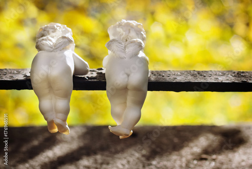 Foto  Funny ceramic angels are back view in autumn park.