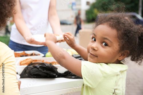 Fotografía  Volunteer sharing food with poor African child outdoors