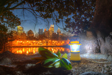Luminous Hand Lantern Standing On The Ground Of Piedmont Park On The Background Of Midtown Atlanta At Dusk
