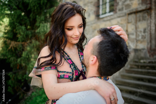 Poster Artist KB Man holds pretty brunette up posing before an old stone building