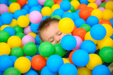 Fototapeta na wymiar A boy in the playing room with many little colored balls