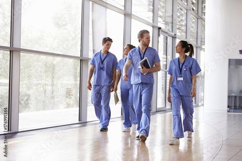 Fotografia  Four healthcare workers in scrubs walking in corridor