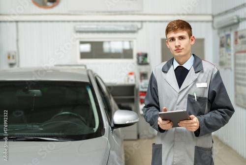 Zdjęcie XXL Portret mechanika samochodowego w warsztacie samochodowym, w tle usługi.