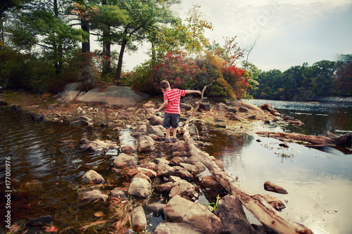 Photo  boy walks the rocks in the water to the side