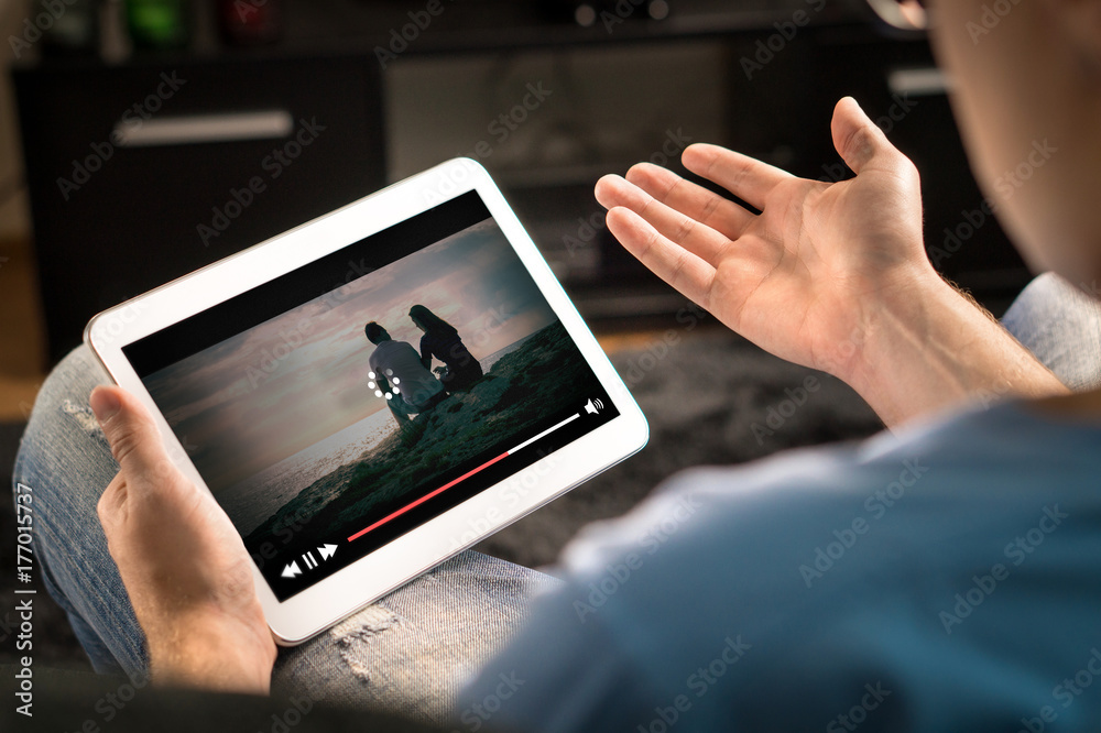 Fototapeta Loading icon rolling on video in an online movie streaming service. Bad and slow internet connection. Film player stopped. Frustrated and confused man watching and holding tablet while spreading arms.