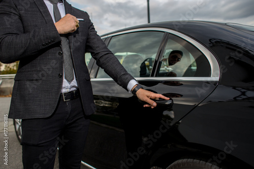 Photographie Man opening a car limousine door