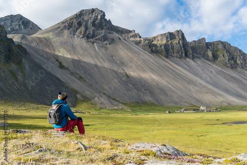 Hombre sentado y mirando a un pueblo Vikingo en la Península de Stokksnes en Isl Wallpaper Mural