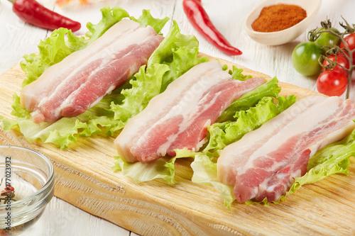 Plakat Surowy wieprzowiny mięsny brisketa bekon na ciapanie desce z sałatą