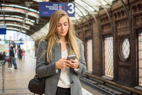 Zdjęcie XXL Młoda kobieta używa telefon przy dworcem.