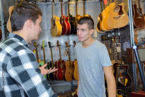 Plakat Młodzi mężczyźni rozmawiają w sklepie z instrumentami muzycznymi