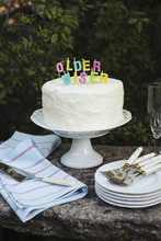 Garden Party With Cake And Candles Saying Older, Wiser On It