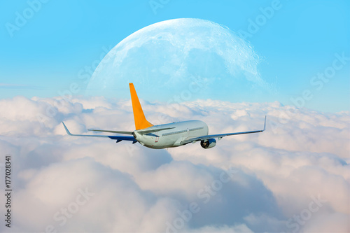 """Plakat Samolot pasażerski w chmurach. podróż samolotem """"Elementy tego zdjęcia dostarczone przez NASA"""""""
